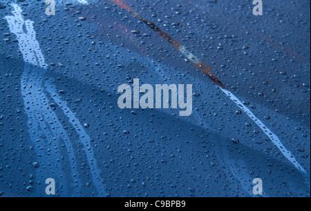 Rain drops on metal car bonnet hood, reflections - Stock Photo