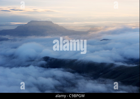 Low lying clouds above with peak rising above at dawn, The Witches, Amphitheatre, Drakensberg, Kwazulu-Natal, South - Stock Photo
