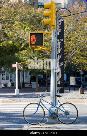 Bicycle Lent up against a Pedestrian crossing sign in New York City - Stock Photo