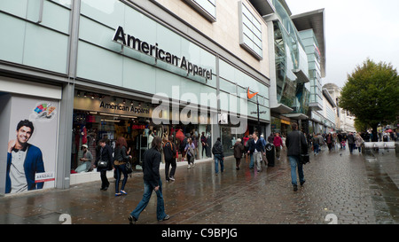 Pedestrians walking past American Apparel store near the Arndale Centre in Central Manchester, England, UK - Stock Photo