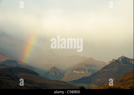 Rainbow at the base of the Amphitheatre range in the Drakensberg Mountains, Royal Natal, Kwazulu-Natal, South Africa - Stock Photo