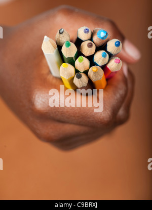 Childs hand gripping colored pencils, Johannesburg, Gauteng Province, South Africa Stock Photo