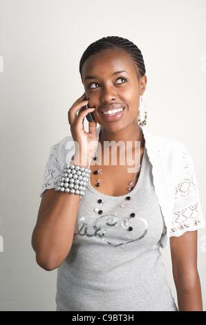 Young Kenyan woman talks on her mobile phone, Nairobi, Kenya - Stock Photo