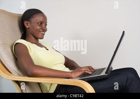 A young Kenyan woman on her laptop, Nairobi, Kenya - Stock Photo