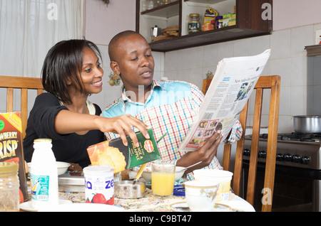Kenyan couple reading paper at breakfast time, Nairobi, Kenya - Stock Photo