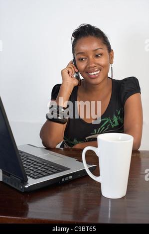 Young Kenyan woman with laptop and phone, Nairobi, Kenya - Stock Photo