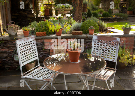 Metal table and chairs on stone patio in english autumn garden - Stock Photo