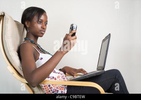 Young Kenyan woman writes an SMS while relaxing with her laptop, Nairobi, Kenya - Stock Photo
