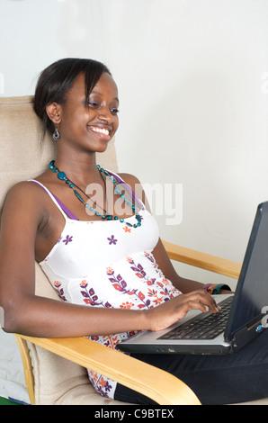 Young Kenyan woman laughs while relaxing with her laptop, Nairobi, Kenya - Stock Photo