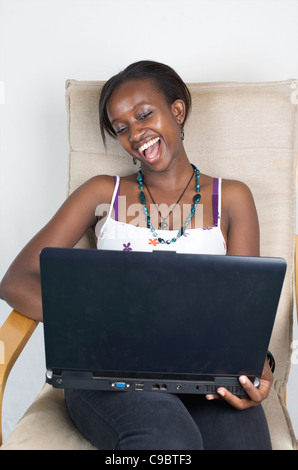 Young Kenyan woman laughs out loud while relaxing with her laptop, Nairobi, Kenya - Stock Photo