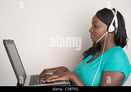Young Kenyan woman works on her laptop and listens to music, Nairobi, Kenya - Stock Photo