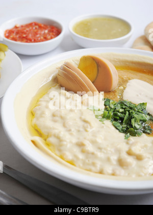 Hummus. A Levantine Arab dip or spread made from cooked, mashed chickpeas, blended with tahini, - Stock Photo