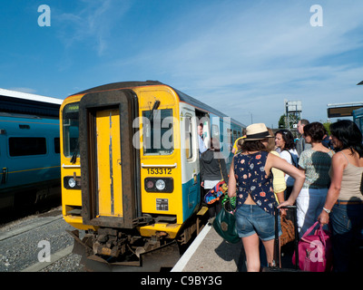 Passengers boarding an Arriva train heading for Tenby at Carmarthen Station, Carmarthenshire Walesd UK - Stock Photo