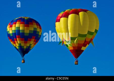 USA, New Mexico, Albuquerque, Balloon Festival. Two colourful hot air balloons in a clear blue sky. - Stock Photo