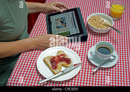 Woman viewing The Times website on an Apple iPad tablet computer at breakfast time - Stock Photo