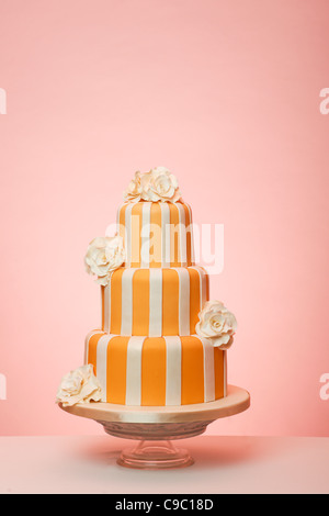 Orange striped wedding cake with peach background - Stock Photo