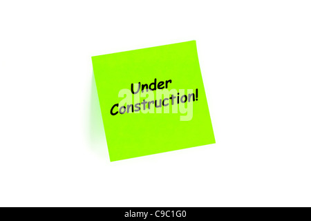 Under Construction On A Note Isolated On White - Stock Photo