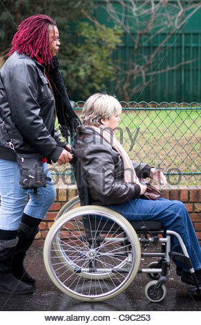 Two women Disabled person in wheelchair being pushed along a street by a friend person disability friendship Paris - Stock Photo