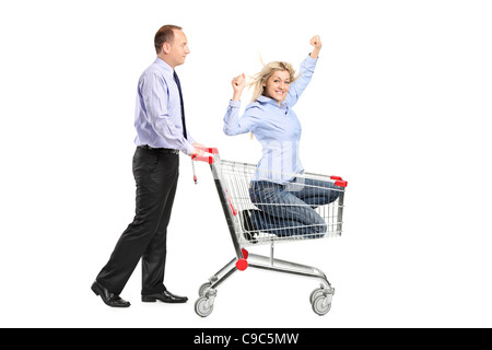 Person pushing a happy woman in a shopping cart - Stock Photo