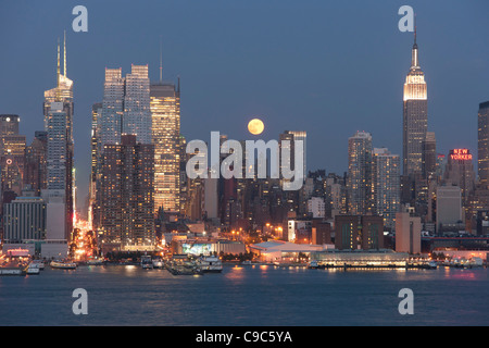 The full moon rises over the Manhattan skyline at twilight as viewed over the Hudson River from New Jersey - Stock Photo