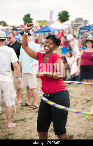 A young lady hula hoops happily at the 'Vintage Virginia Wine Festival' in Manassas Virginia. - Stock Photo