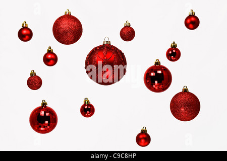 A selection of red Christmas baubles on a white background. - Stock Photo