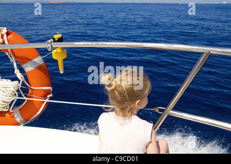 Blond little girl rear view sailing in boat in blue Ibiza sea - Stock Photo