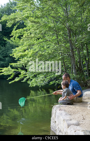 Father teaching son how to fish - Stock Photo