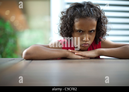 Sulky girl scowling at camera - Stock Photo