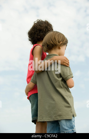 Young siblings standing together outdoors - Stock Photo