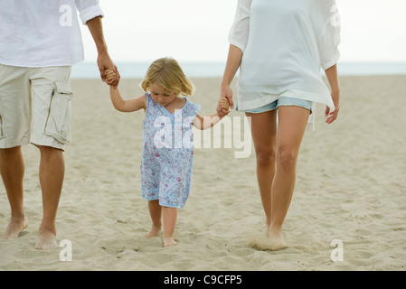 Little girl walking on beach with her parents, cropped - Stock Photo