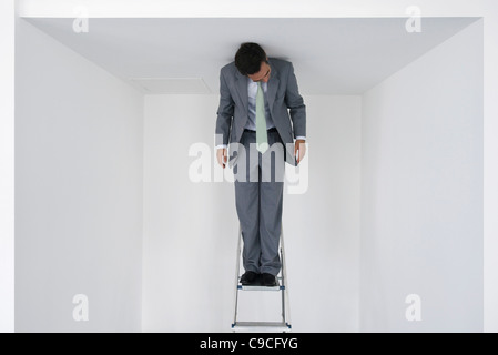 Executive standing on stepladder - Stock Photo