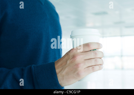 Man holding disposable coffee cup, cropped - Stock Photo