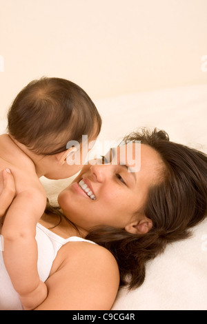 Mom and son on bed and mother embracing the 5 Months old infant baby playing with him - Stock Photo