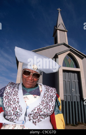Namibia Southern Africa Township of Walvis Bay Herero woman wearing sunglasses in Mondesa standing next to a Presbyterian - Stock Photo