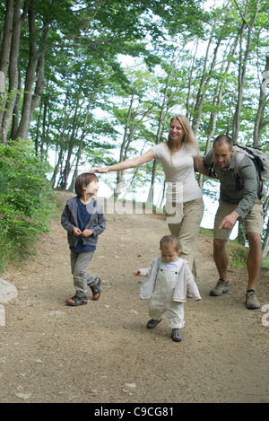 Parents playing with children in woods - Stock Photo