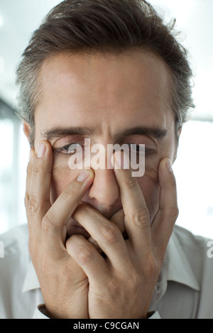 Man with hands covering face - Stock Photo