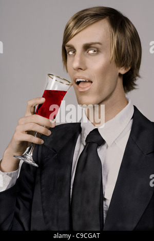 handsome young vampire drinking form Champaign glass - Stock Photo