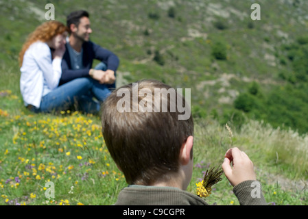 Boy playing with wildflowers, rear view - Stock Photo