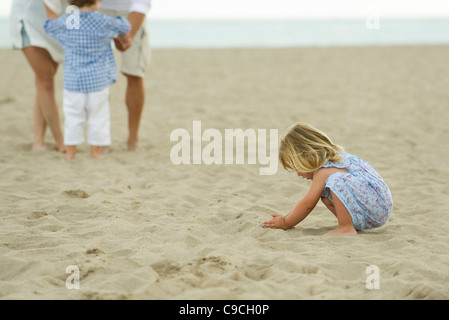 Little girl playing in sand at the beach, family in background - Stock Photo
