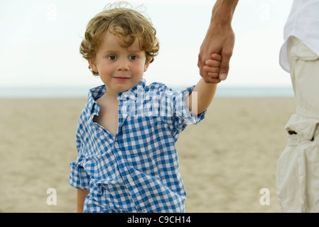 Little boy holding father's hand at the beach, cropped - Stock Photo