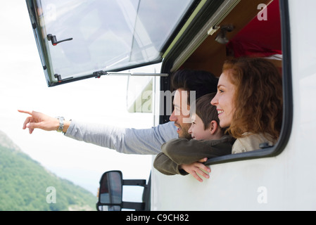 Parents with young son in motor home, father pointing into distance - Stock Photo