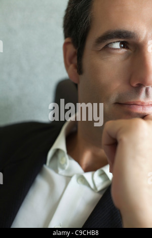 Executive with hand under chin, close-up, cropped - Stock Photo