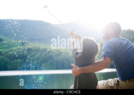 Father and son fishing, boy caught fish in fishing net - Stock Photo