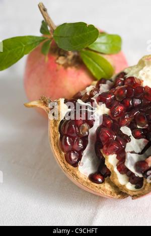 Fresh pomegranates, one cut open revealing seeds - Stock Photo