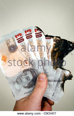Burnt £10 notes, UK currency. - Stock Photo