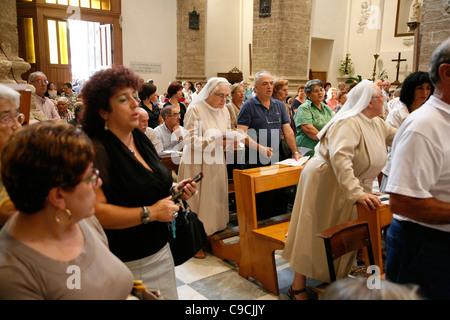 People attending mass at Chiesa di San Michele church, Alghero, Sardinia, Italy. - Stock Photo