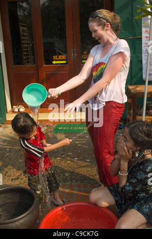 Tourist pouring water on a young Lao boy, Lao New Year (Pi Mai Lao), Luang Prabang, Laos - Stock Photo