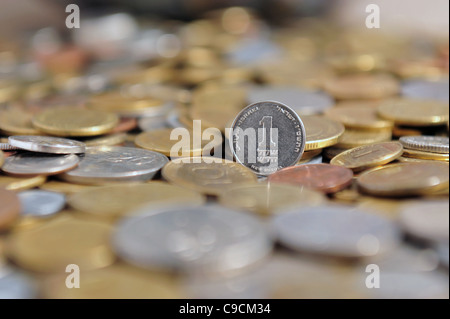 One new Israeli shekel coin with other coins from other currencies and countries - Stock Photo