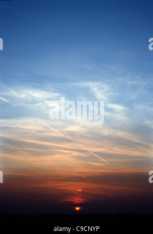 Aircraft contrails dissolving into the sunset in the sky above Tempelhof Airport in Berlin. - Stock Photo